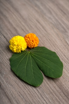 Indian festival dussehra, showing golden leaf (bauhinia racemosa) and marigold flowers on a wooden table.