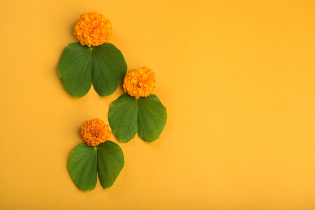 Indian festival dussehra, showing golden leaf (bauhinia racemosa) and marigold flowers on a yellow background.