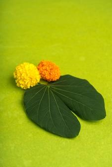 Indian festival dussehra, showing golden leaf and marigold flowers on brown.
