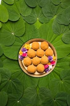 インドの祭りダシャラ、象徴的なゴールデンまたはピリオスティグマの葉、またはアプタパティとしても知られるバウヒニアラセモサは、ブーンディまたはモチクールラドゥーが中央のプレートで提供される円形パターンに配置されています