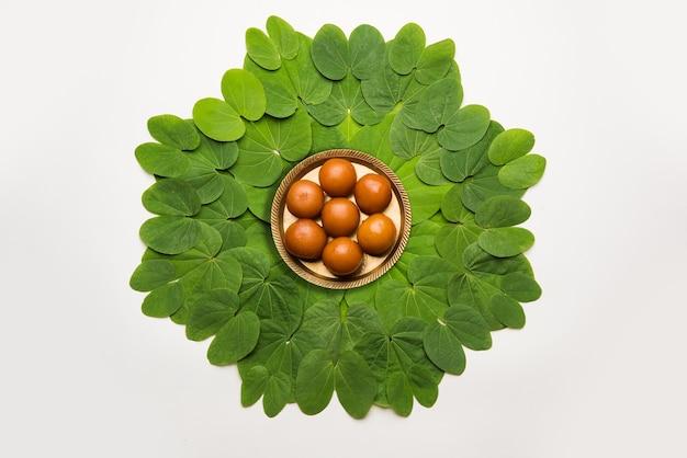 インドの祭りダシャラ、象徴的なゴールデンまたはピリオスチグマの葉、またはアプタパティとしても知られているバウヒニアラセモサは、中央のプレートにグラブジャムンの甘いものを円形に配置し、選択的に焦点を当てています