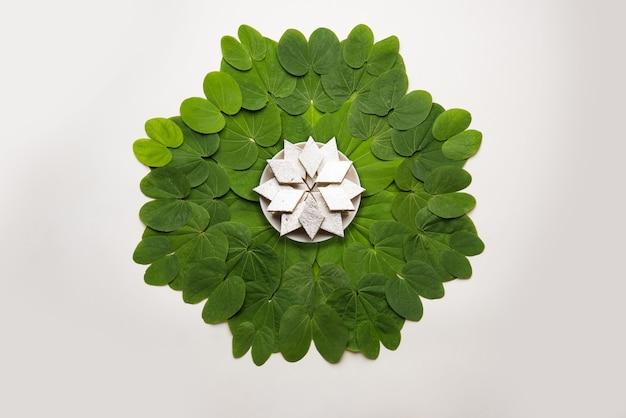インドの祭りダシャラ、象徴的なゴールデンまたはピリオスチグマの葉、またはアプタパティとしても知られるバウヒニアラセモサは、中央のプレートにカジュカトリの甘いブルフィが円形に配置されています