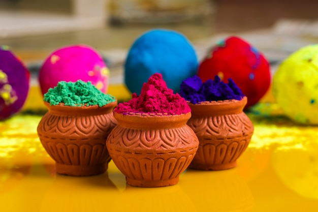 Indian festival holi, multicolor's wooden bowl on yellow surface