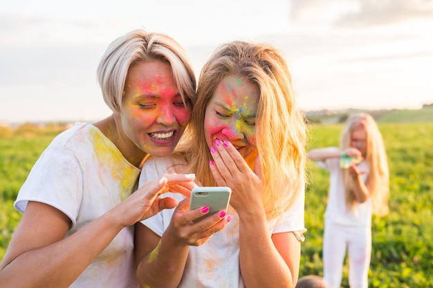 Indian festival of holi, people concept - two laughing girls with colourful powder on the faces look