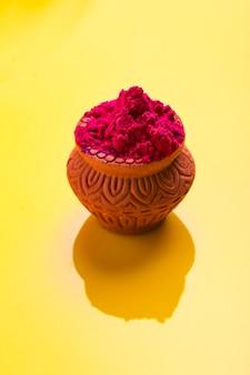 Индийский фестиваль холи: красный цвет в деревянной глиняной миске