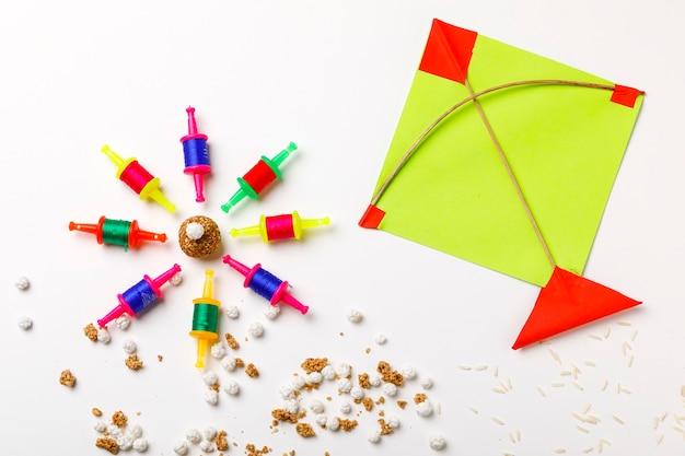 インドのお祭りマカールサンクランティのコンセプト、カラフルな凧、ひも、甘いゴマの種のボール。