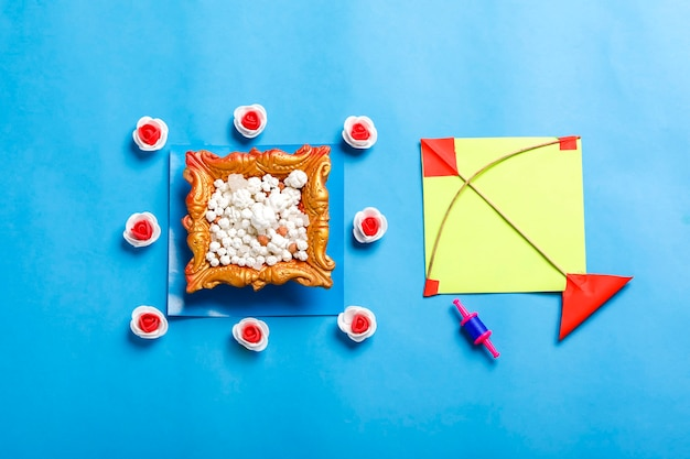 Indian festival makar sankranti concept, colorful kite ,string and sweet sesame seed ball.