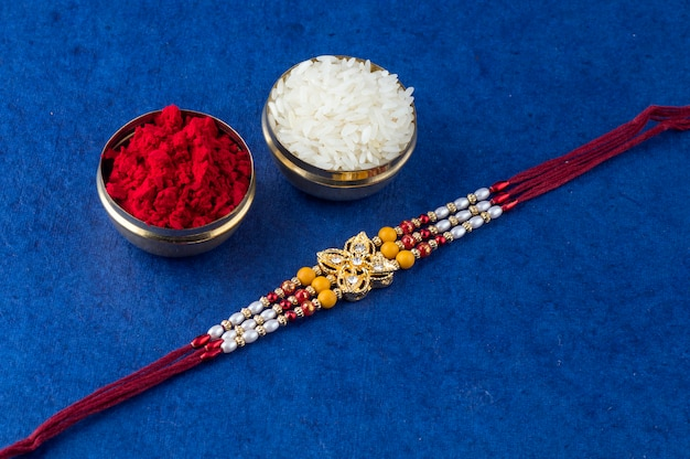 Indian festival raksha bandhan background with an elegant rakhi, rice grains and kumkum.