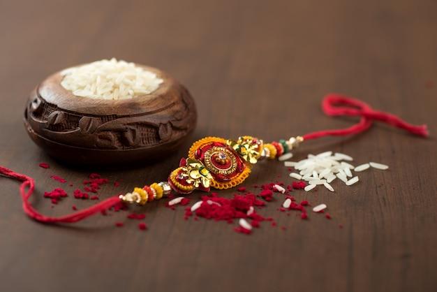 인도 축제 : 우아한 rakhi, rice grains 및 kumkum이있는 raksha bandhan. 형제 자매 사랑의 상징 인 인도 전통 손목 밴드.