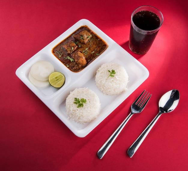 Индийское карри рыбы и рис служили в белой квадратной тарелке над красочным фоном. подается с холодным напитком
