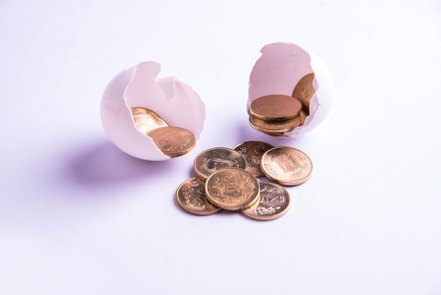 白い背景の上に分離された、ひびの入った卵から出現するインドの5ルピーの黄金のコイン