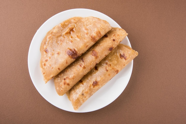 Indian flat bread known as plain paratha or roti served in a quarter plate, selective focus
