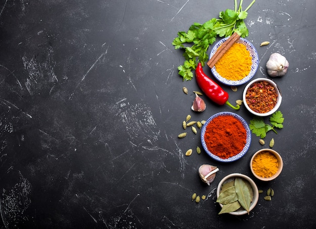 인도 음식 요리 배경입니다. 전통적인 인도 향신료와 재료. 카레, 강황, 카다몸, 마늘, 후추, 신선한 고수, 계피. 이국적인 식사를 준비합니다. 상위 뷰, 텍스트를 위한 공간