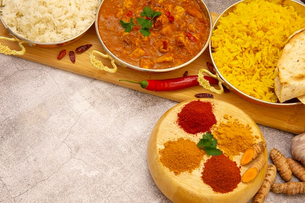 Indian food. curry chicken in tomato sauce with white and yellow rice, spices: curry, turmeric, hot and mild paprika. copy space