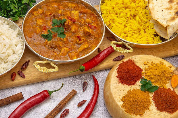 Indian food. curry chicken in tomato sauce with white and yellow rice, spices: curry, turmeric, hot and mild paprika