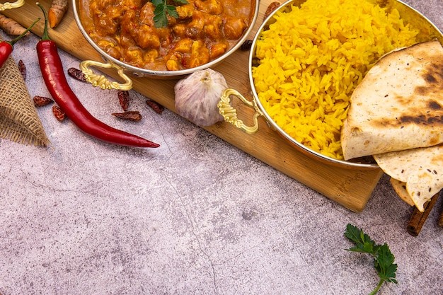 Indian food. curry chicken in tomato sauce and yellow rice, copy space