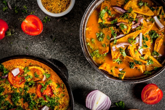 Indian food recipes, masala omelette with and indian omelet masala egg curry, with fresh vegetables - tomato, hot chili pepper, parsley dark stone ,  copyspace top view