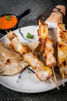 Индийская кухня. традиционное блюдо с пикантной курицей, тикка масала, сливочное куриное карри, с индийским нааном, сдобным хлебом, специями, зеленью. подается в миске. соус, на шампурах. каменный темный стол. copyspace