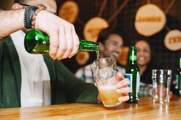 Индийские друзья в пабе. парни и девушка в баре. праздник за кружкой пива.