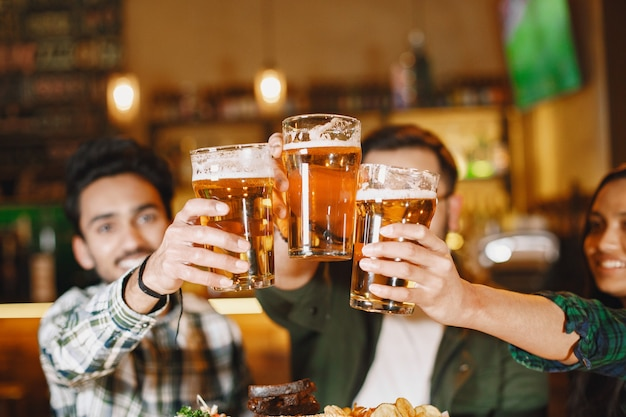 Amici indiani in un pub. ragazzi e ragazza al bar. celebrazione davanti a un boccale di birra.