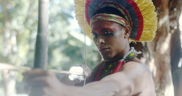 Индеец из племени патаксон использует лук и стрелы. день индии. бразильский индийский