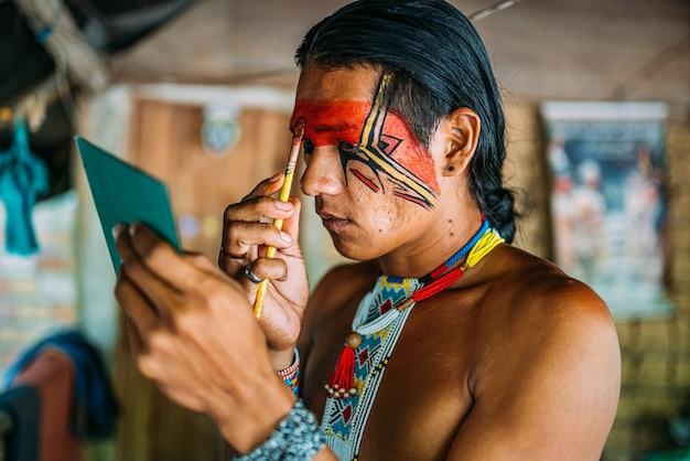 パタクセ族のインディアン、鏡を使ってフェイスペインティングをしている