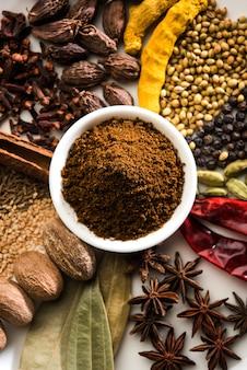 Индийский порошок гарам масала в миске и его ингредиенты красочные специи. подается на мрачном фоне. выборочный фокус