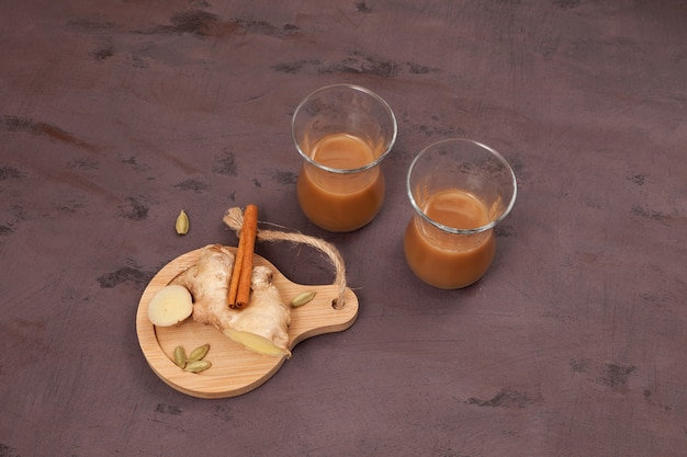 Indian ginger tea with milk and spices on brown