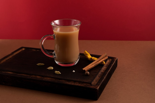 Indian ginger tea with milk and spices on red