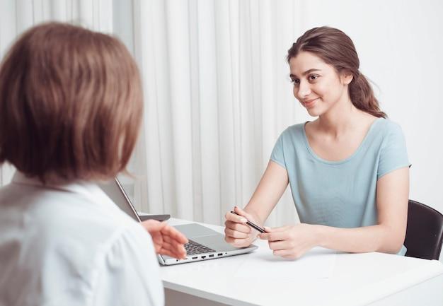 Индийская девушка советует клиенту женщине. женщины дружелюбно разговаривают, сидя в офисе.