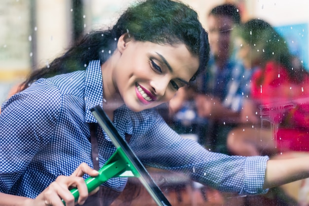 Indian girl cleaning windows
