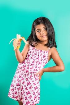 Индийская девушка ест банан, стоя изолированные на зеленом фоне