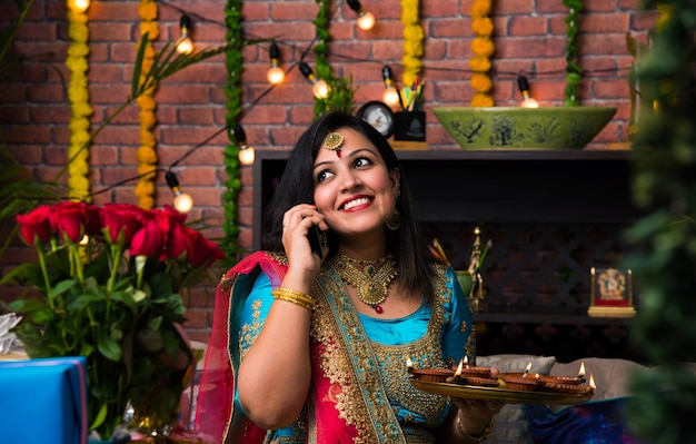 Индийская девушка держит дивали-дийя в традиционной одежде, щелкая изображение селфи или разговаривая по смартфону.