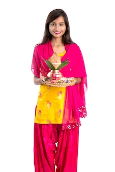 Indian girl holding a traditional copper kalash with pooja thali