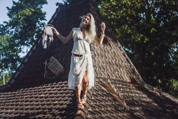 屋根の上のインドの女の子。ドリームキャッチャー。ドリームキャッチャーと美しいブロンドの女の子。