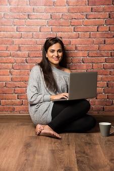 赤レンガの壁に対して木の床の上に座っているラップトップを持つインドの女の子または女性