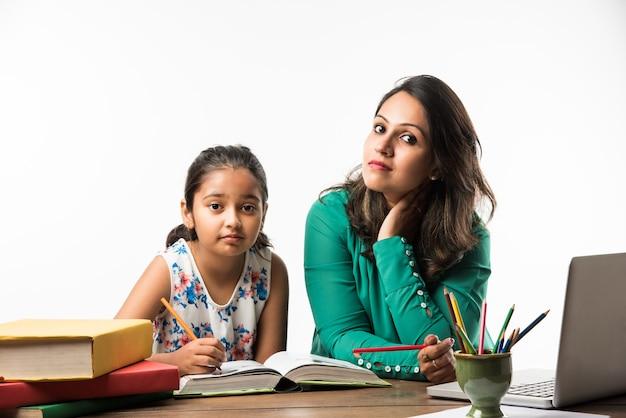 Индийская девушка учится с матерью или учителем за учебным столом с портативным компьютером, книгами и весело учится