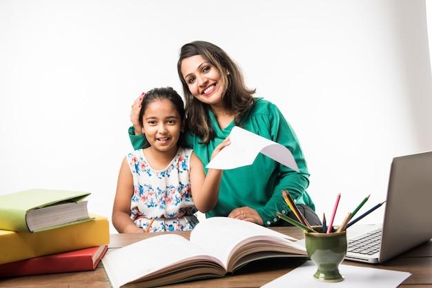 ラップトップコンピューター、本と勉強のテーブルで母親や教師と一緒に勉強し、楽しく学ぶインドの女の子