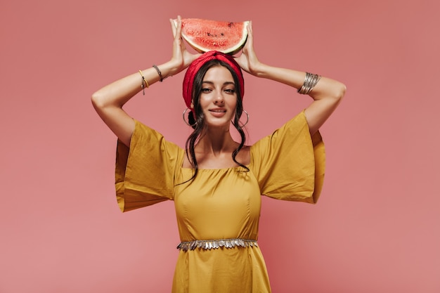 Indian girl with black wavy hair in headband and yellow fashionable clothes holding watermelon on her head on pink wall