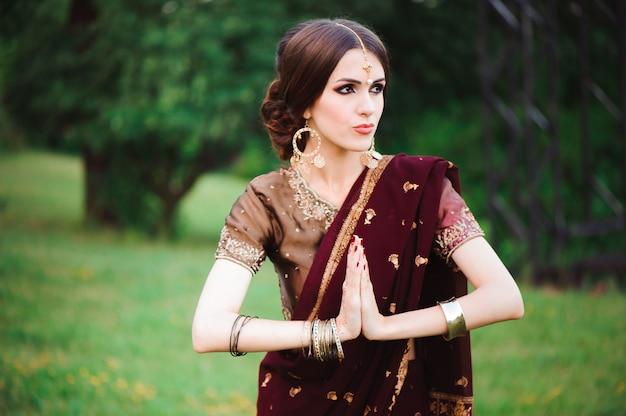 Индийская девушка с восточными украшениями и хной для макияжа, нанесенной на руку. девушка брюнет индусской модели с индийскими драгоценностями.