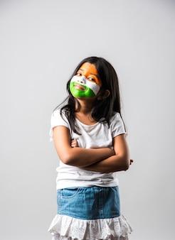 삼색으로 만든 종이 풍차 장난감을 가진 인도 소녀와 인도 국기 색으로 칠해진 얼굴. 행복한 독립 기념일이나 공화국 기념일 인사말에 적합합니다.