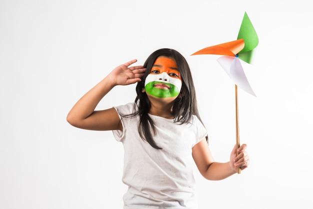 삼색 또는 인도 국기 색상으로 구성된 종이 풍차 장난감을 가진 인도 소녀. 해피 독립 기념일 또는 공화국 기념일 인사말에 적합합니다.
