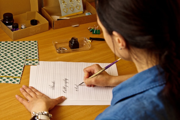 Indian girl writes with ink pen on a white paper sheet. stationery on a wooden desk