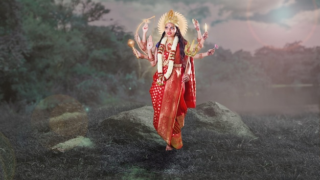 붉은 사리를 입고 호수 근처에 서 있는 8개의 손을 가진 인도 여신 두르가