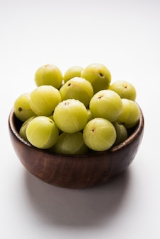 Indian gooseberry or amla (phyllanthus emblica) in a cane basket over colourful or wooden surface, selective focus