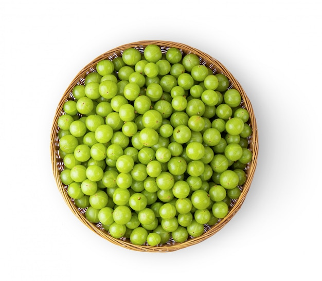 Indian gooseberry in basket on white wall.