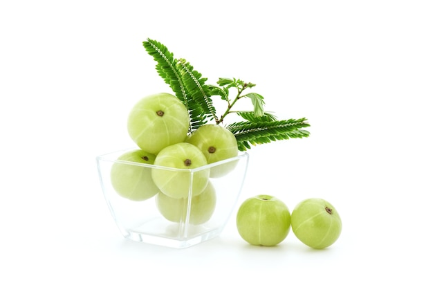 Indian gooseberry or phyllanthus emblica fruits and green leaves isolated on white .
