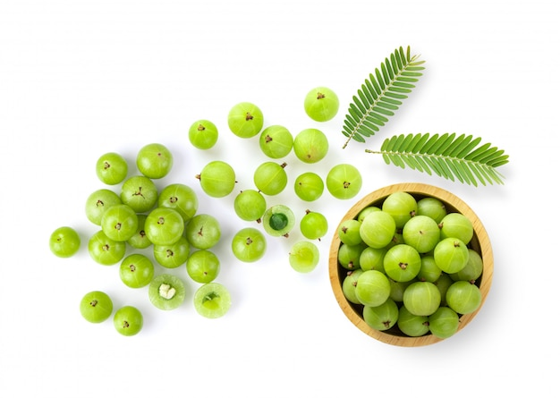 Indian gooseberry with leaves on white wall.