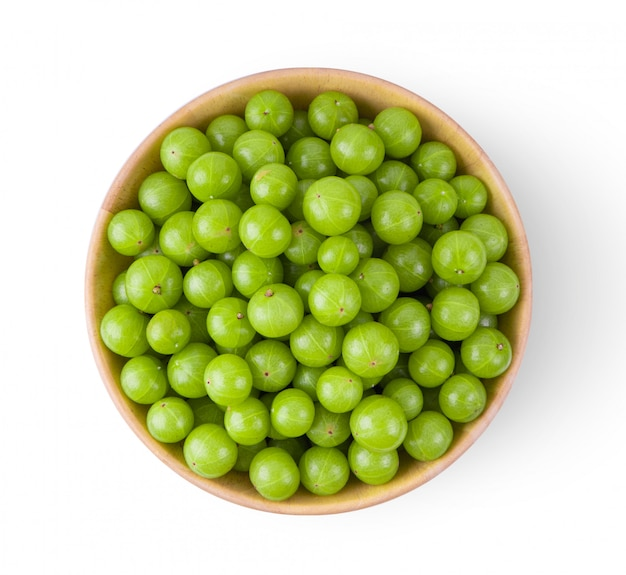 Indian gooseberry in wood bowl on white wall