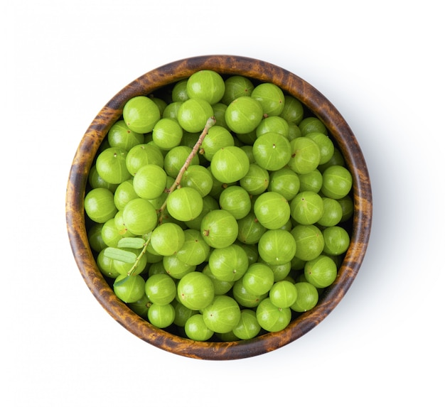 Indian gooseberry in wood bowl on white wall.